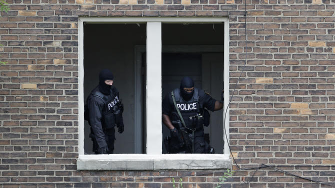 Authorities search an abandoned building for a man who escaped a courthouse in Detroit, Monday, Sept. 9, 2013. Derreck White, 25, who police said also used the name Abraham Pearson, was awaiting sentencing in an armed robbery and escaped a Detroit courthouse on Monday after stabbing a sheriff's deputy several times in the neck and carjacking a motorist. The escape prompted a lockdown of the facility and sparked a manhunt. (AP Photo/Paul Sancya)