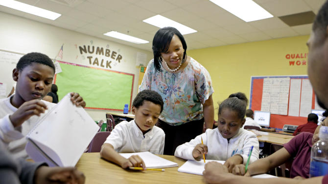 In this Thursday, April 18, 2013 photo, Burgess-Peterson Elementary School principal Robin Robbins, center, meets with students during Atlanta Public School's after-school remediation program in Atlanta. Anxiety is high among students and teachers with state standardized tests set to begin Tuesday. A lot of focus and criticism has been aimed at the tests, known as CRCT in Georgia, since one of the nation's largest cheating scandals erupted within the Atlanta Public Schools system a few years back that included allegations that teachers and principals changed scores to inflate performance. While criminal charges are pending against 35 former Atlanta educators, the district has been working on a system-wide remediation program aimed at helping those directly affected by the cheating scandal and others who have simply fallen behind. (AP Photo/David Goldman)
