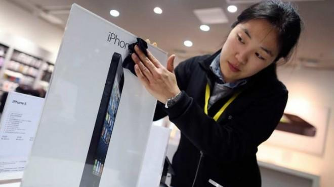 An employee cleans an advertisement plate at an Apple store in Wuhan, China, on the eve of iPhone 5's Chinese debut.