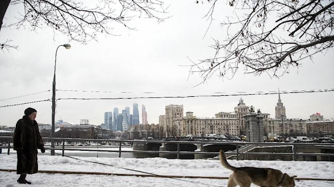 """A woman walks her dog with the skyscrapers of the """"Moscow City"""" left in the background in Moscow, Russia, Friday, Jan. 30, 2015. Russia's central bank has cut a key interest rate, which it had hiked in previous months to support the ruble, in order to help the economy. (AP Photo/Pavel Golovkin)"""