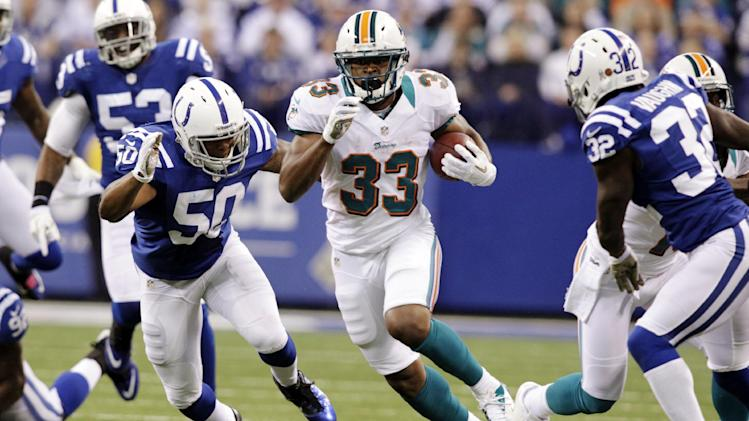Miami Dolphins running back Daniel Thomas, center, picks up yardage as he gets between Indianapolis Colts inside linebacker Jerrell Freeman, left, and cornerback Cassius Vaughn during the first half of an NFL football game in Indianapolis, Sunday, Nov. 4, 2012. (AP Photo/AJ Mast)