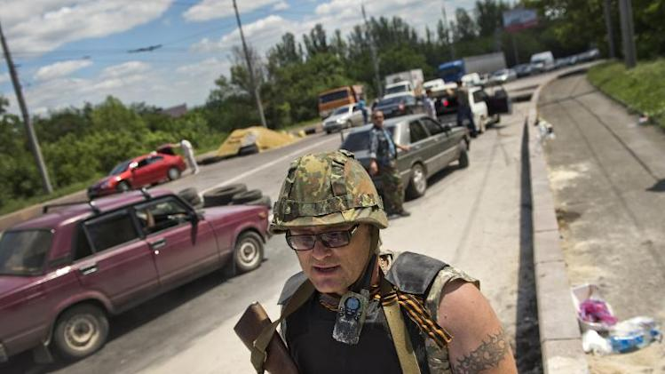 """A pro-Russian militia man from the """"Russian Orthodox Army"""" stands at a check point near the airport in Donetsk city on June 10, 2014"""