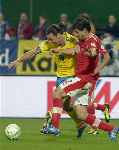 Sweden's Zlatan Ibrahimovic and Austria's Gyoergy Garics challenge for the ball during a World Cup 2014 Group C qualifying soccer match between Austria and Sweden in Vienna, Austria, Friday, June 7, 2