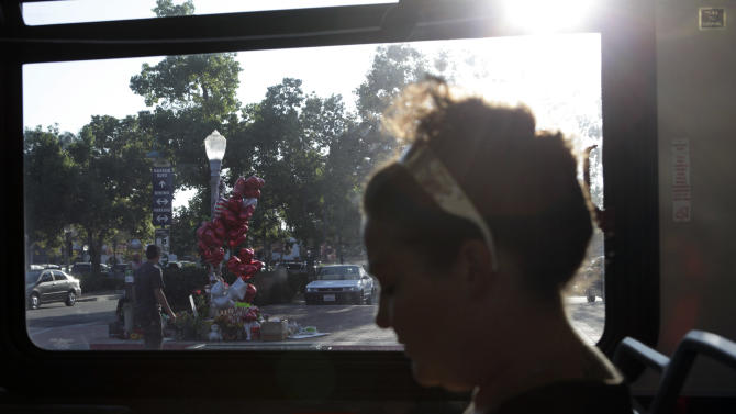 Kimberly Holifield sits in a bus as a man visits the memorial site for Kelly Thomas in Fullerton, Calif., Thursday, Aug. 18, 2011. Until last month, the most pressing political issue in the Southern California suburb of Fullerton was a debate over whether to build homes and retail on hundreds of acres of rolling hills north of the city. Today, the historic town that's home to five colleges and a vibrant nightlife is the target of international outrage after the mentally ill homeless man died following a violent fight with six police officers that was captured on camera. (AP Photo/Jae C. Hong)