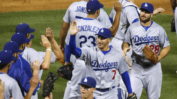 Los Angeles Dodgers' Alex Guerrero (7) is congratulated by teammates the second game of a baseball doubleheader between the Dodgers and the Colorado Rockies on Tuesday, June 2, 2015, in Denver. The Dodgers won 9-8 behind Guerrero's grand slam in the ninth inning. (AP Photo/David Zalubowski)