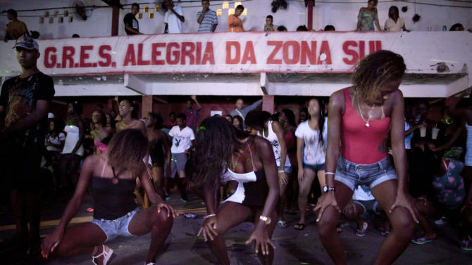 """In this Feb. 3, 2012, women dance during a funk """"baile,"""" or party, in the Cantagalo slum in Rio de Janeiro, Brazil. Its market potential has become hard to ignore: A recent survey by the Brazilian think tank the Getulio Vargas Foundation found funk disc jockeys, MCs and others generate about $720 million a month in revenue. (AP Photo/Felipe Dana)"""