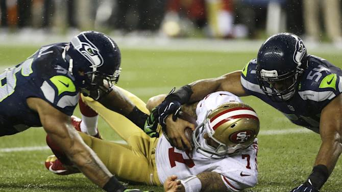 San Francisco 49ers quarterback Colin Kaepernick (7) is tackled by Seattle Seahawks' Bobby Wagner, right, and Leroy Hill, left, in the first half of an NFL football game, Sunday, Dec. 23, 2012, in Seattle. (AP Photo/Elaine Thompson)