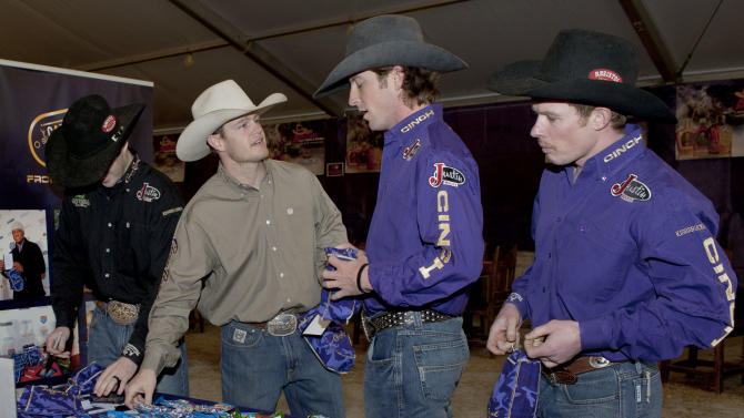 IMAGE DISTRIBUTED FOR CROWN ROYAL - Crown Royal Riders Steve Woolsey (from right), Tilden Hooper, Cody Whitney and Wesley Silcox pack Crown Royal CAMO Care Packages, Saturday, Feb. 9, 2013, at the San Antonio Stock Show and Rodeo in San Antonio. (Darren Abate/AP Images for Crown Royal)