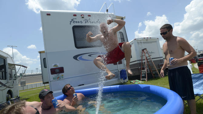 Ted Georges, of Columbus, Ohio, jumps into a pool from a recreational vehicle as Andrew Florance, left, of Naples, Fla., sprays him while trying to beat the heat before the races in the infield of the Daytona International Speedway auto race in Daytona Beach, Fla., Friday, July 6, 2012. Watching them are Chris Fuqua, second from left, Zach Crandell, center, and Bob Holtz, right. (AP Photo/Phelan M. Ebenhack)