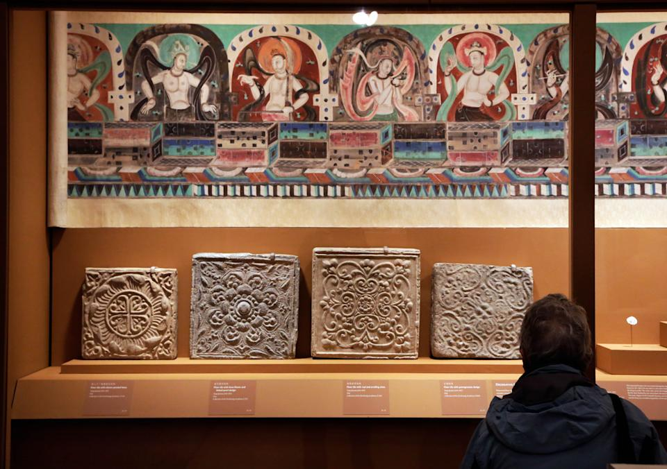 "Decorative floor tiles, and ""Celestial Music"" from Mogao Cave 288, are displayed in ""Dunhuang: Buddhist Art at the Gateway of the Silk Road,"" at the China Institute, in New York,  Tuesday, April 24, 2013. (AP Photo/Richard Drew)"