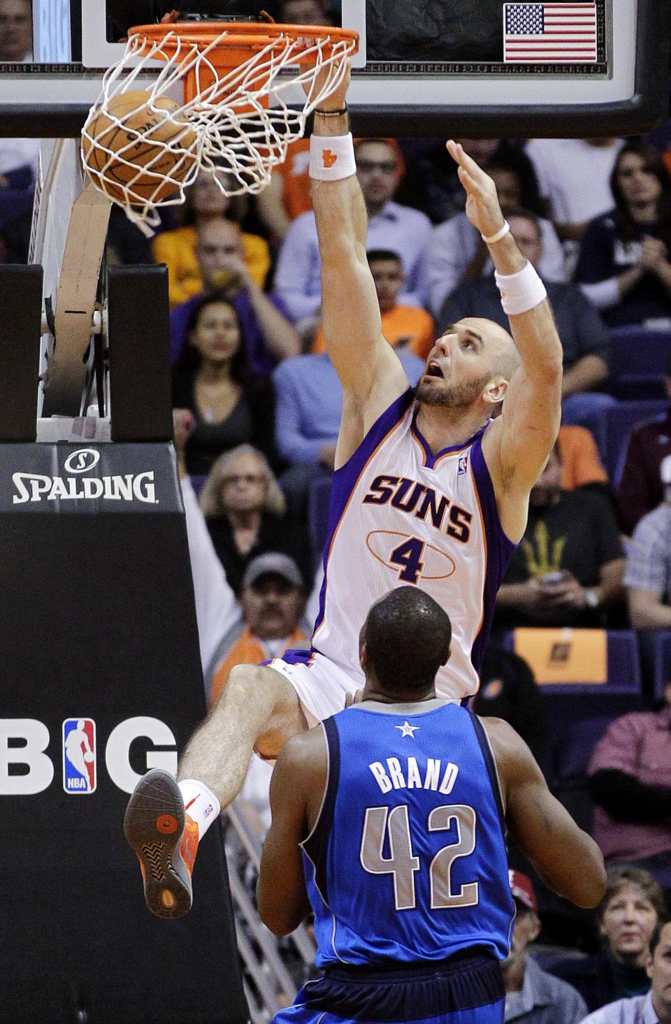 Phoenix Suns' Marcin Gortat, of Poland, dunks over Dallas Mavericks' Elton Brand (42) during the first half of an NBA basketball game, Thursday, Dec. 6, 2012, in Phoenix. (AP Photo/Matt York)