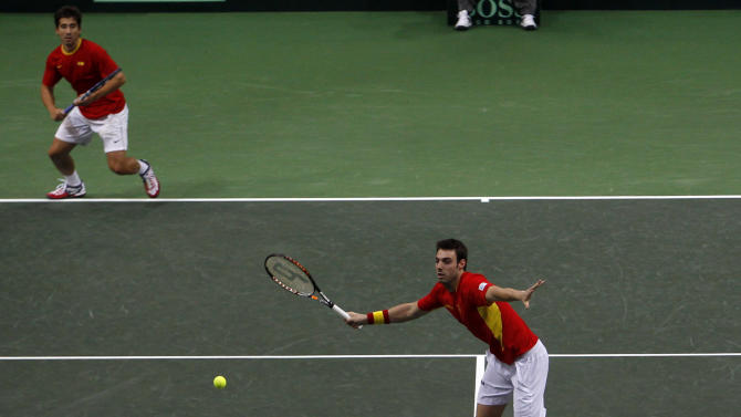 Spain's Marcel Granollers, center, returns a ball while his doubles partner Marc Lopez, back, follows the play during their Davis Cup finals doubles tennis match against Czech Republic's Radek Stepanek, right, and Tomas Berdych, front, in Prague, Czech Republic, Saturday, Nov. 17, 2012. (AP Photo/ Marko Drobnjakovic)