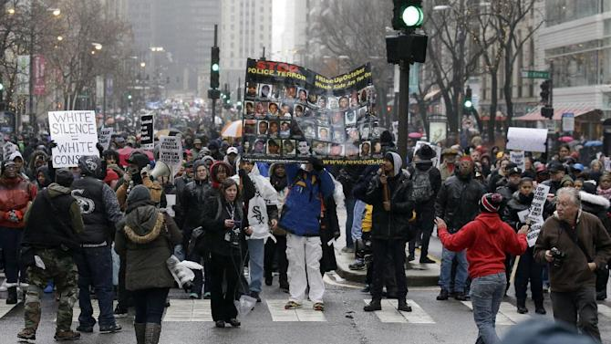 "Protesters make their way up North Michigan Avenue on Friday, Nov. 27, 2015, in Chicago as community activists and labor leaders hold a demonstration billed as a ""march for justice""  in the wake of the release of video showing an officer fatally shooting Laquan McDonald. (AP Photo/Nam Y. Huh)"