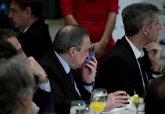 Real Madrid's President Florentino Perez, centre, speaks on a cell phone next to Atletico de Madrid's CEO, Miguel Angel Gil Marin, right during a breakfast sports meeting in a hotel in Madrid,