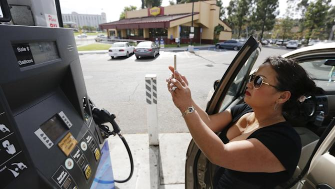Lorena Delara takes a picture of the total she paid after filling up her tank with gasoline at a gas station Friday, Oct. 5, 2012, in San Diego. Delara paid $81.27 for a little over 15 gallons of gas. A 20-cent jump overnight in California gas prices has put the state ahead of Hawaii for the nation's most expensive gas. (AP Photo/Gregory Bull)