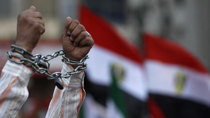 A protester shows his chained hands during a demonstration against a constitution drafted by Islamist supporters of President Mohammed Morsi in Tahrir square in Cairo, Egypt, Friday, Dec. 14, 2012. Opposing sides in Egypt's political crisis were staging rival rallies on Friday, the final day before voting starts on a contentious draft constitution that has plunged the country into turmoil and deeply divided the nation.(AP Photo/Petr David Josek)