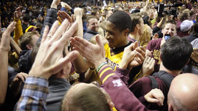 Minnesota's Rodney Williams Jr., center, is surrounded by fans as he leaves the court after defeating Indiana 77-73 in an NCAA college basketball game, Tuesday, Feb. 26, 2013, in Minneapolis. (AP Photo/Tom Olmscheid)