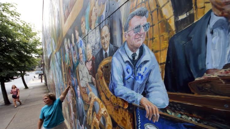 A woman touches a mural in downtown State College, Pa., featuring former Penn State head football coach Joe Paterno, center, on Monday, July 23, 2012. Penn State football was all but leveled Monday by an NCAA ruling that wiped away 14 years of coach Joe Paterno's victories and imposed a mountain of fines and penalties, crippling a program whose pedophile assistant coach spent uncounted years molesting children, sometimes on university property. (AP Photo/Gene J. Puskar)