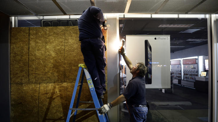Dwayne Wallace, left, and Brian Rogers board up an AT&T store in Rehoboth Beach, Del. on Saturday, Oct. 27, 2012 as Hurricane Sandy approaches the east coat. (AP Photo/Alex Brandon)