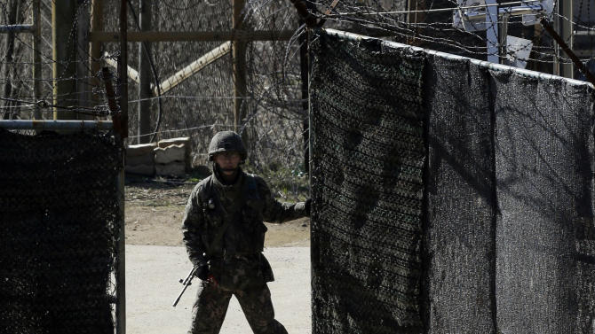 A South Korean soldier closes a military gate in Paju, north of Seoul, South Korea, Sunday, April 7, 2013. A top South Korean national security official said Sunday that North Korea may be setting the stage for a missile test or another provocative act with its warning that it soon will be unable to guarantee diplomats' safety in Pyongyang. But he added that the North's clearest objective is to extract concessions from Washington and Seoul. (AP Photo/Lee Jin-man)