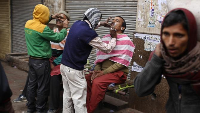 Men get their shave and moustache groomed by roadside barbers on a winter morning in the old quarters of Delhi