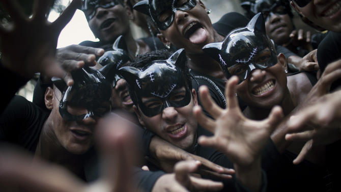 """Revelers dressed as cat-woman joke as they pose for photos during the """"Cordao da Bola Preta"""" street carnival parade in Rio de Janeiro, Brazil, Saturday, Feb. 9, 2013. According to Rio's tourism office, Rio's street Carnival this year will consist of 492 block parties, attended by an estimated five million Carnival enthusiasts. (AP Photo/Felipe Dana)"""