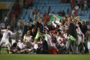 Iran's national soccer team celebrate after defeating South Korea in their World Cup qualifying soccer match in Ulsan