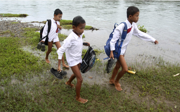 Elementary school boys carry their shoes and bags after crossing a river to go to school in Indonesia's West Sumatra province