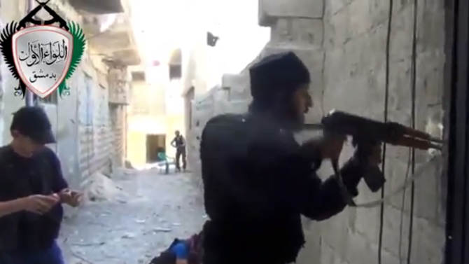 """In this image taken from video obtained from the Ugarit News, which has been authenticated based on its contents and other AP reporting, Syrian rebels clash with government forces in Damascus, Syria, Friday, May 3, 2013. Syria's main opposition group on Friday accused President Bashar Assad's regime of committing a """"large-scale massacre"""" in a Sunni village near the Mediterranean coast, killing scores of people, according to activists. (AP Photo/Ugarit News via AP video)"""