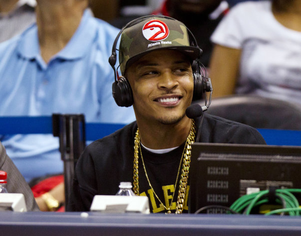 Rapper T.I. sits at the broadcast table as he helps call the action in the first half of an NBA basketball game between Miami Heat and Atlanta Hawks in Atlanta, Friday, Nov. 9, 2012. (AP Photo/John Bazemore)