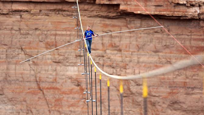 FILE _ In this June 23, 2013 file photo provided by the Discovery Channel, aerialist Nik Wallenda walks a 2-inch-thick steel cable taking him a quarter mile over the Little Colorado River Gorge, Ariz. Television executives are looking for more than hot actors these days. With ratings for Wallenda's tightrope walks across Niagara Falls and the Grand Canyon in mind, networks have taken meetings from people wanting to show cars flipping over, or set a record for simultaneous skydiving. (AP Photos/Discovery Channel, Tiffany Brown, File)