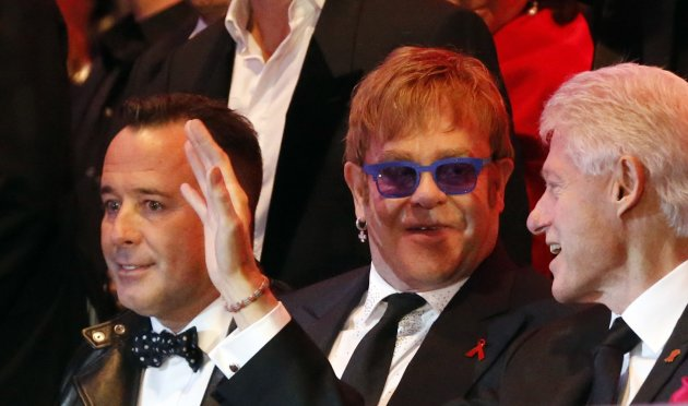 Elton John and his partner David Furnish listen to former U.S. President Bill Clinton during the opening ceremony of the 21st Life Ball in Vienna