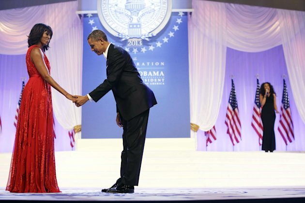"President Barack Obama bows as he and first lady Michelle Obama, wearing a ruby colored chiffon and velvet Jason Wu gown, gets ready to dance as singer Jennifer Hudson, right, sings Al Green's ""Let's"