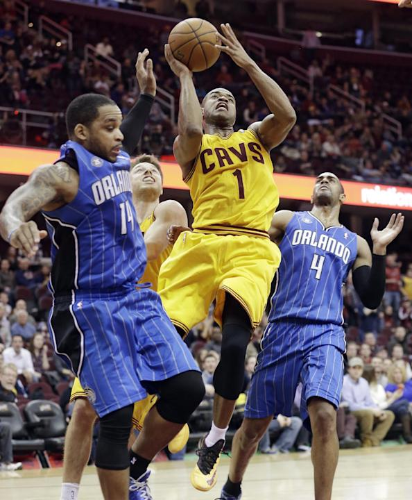 Cleveland Cavaliers' Jarrett Jack (1) shoots  between Orlando Magic's Jameer Nelson (14) and Arron Afflalo (4) during overtime in an NBA basketball game Thursday, Jan. 2, 2014, in Cleveland. T
