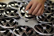 An employee of German car maker Volkswagen takes a logo of the company to fix it on a car