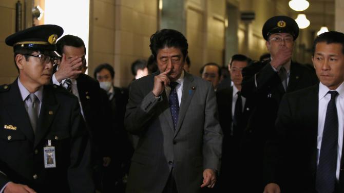 Japan's PM Abe walks as he leaves a lower house committee session at the parliament in Tokyo