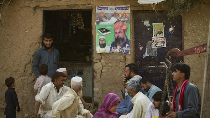 People sit outside a campaign office of a candidate in Pakistan's nationwide elections in Islamabad's slums on Tuesday, May 14, 2013 in Pakistan. The final vote count from weekend's nationwide elections in Pakistan on Tuesday confirmed a big win for former Prime Minister Nawaz Sharif's party. (AP Photo/B.K. Bangash)