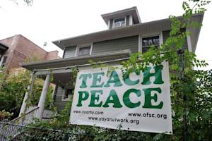A banner urging schools to 'teach peace' hangs across …