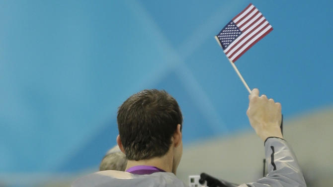 United States' Michael Phelps waves the American Flag after getting his 18th gold medal at the Aquatics Centre in the Olympic Park during the 2012 Summer Olympics in London, Saturday, Aug. 4, 2012. (AP Photo/Matt Slocum)