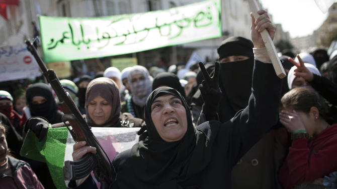 A woman holds a machine gun during an anti government slogans in a town in north Syria, Friday, March 2, 2012. Syria has faced mounting international criticism over its bloody crackdown on the uprising, which started with peaceful protests but has become increasingly militarized. (AP Photo/Rodrigo Abd)
