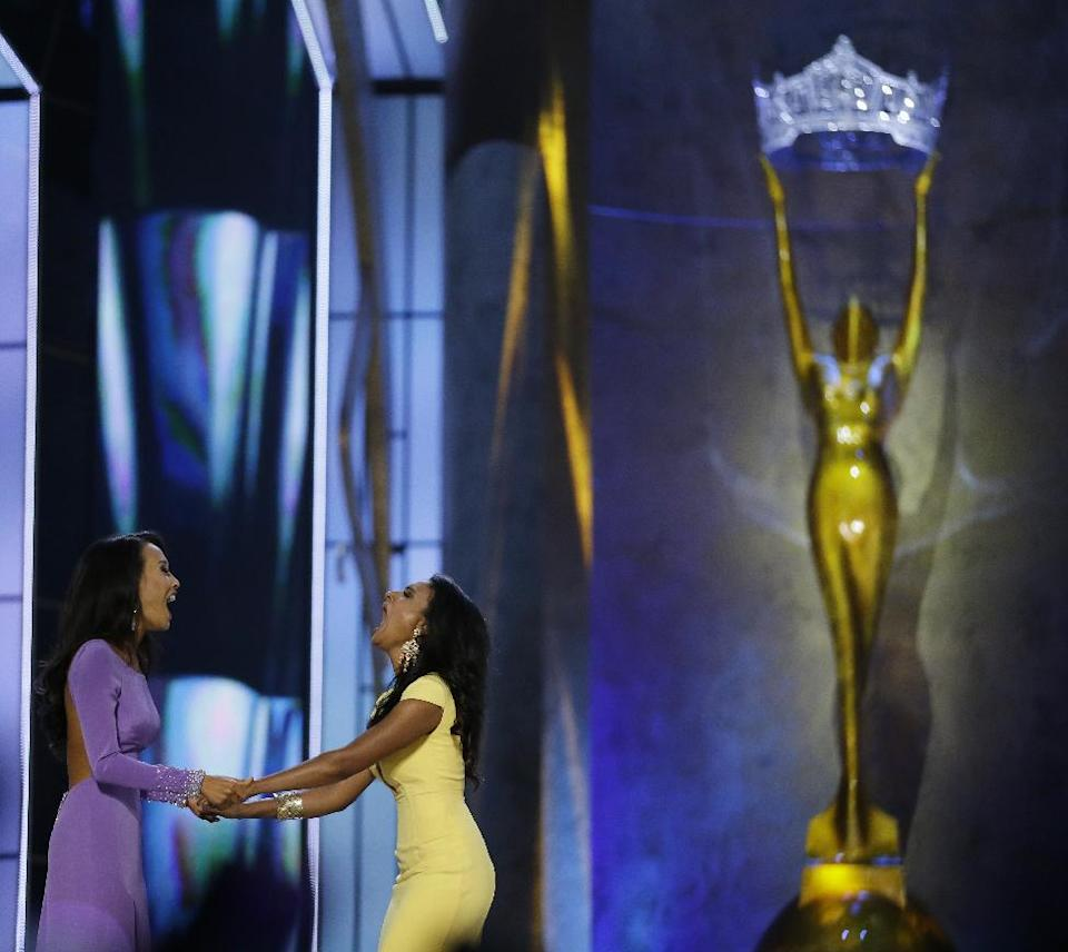 Miss New York Nina Davuluri, right, reacts with Miss California Crystal Lee after Davuluri won Miss America 2014 pageant, Sunday, Sept. 15, 2013, in Atlantic City, N.J. (AP Photo/Julio Cortez)
