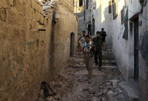 Free Syrian Army fighters walk with their weapons along a street around Hanano Barracks in Aleppo