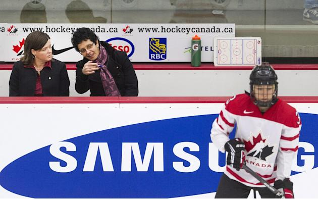 Canada's coaches Danielle Goyette, center, and Lisa Haley watch from the bench as Canada's Jocelyn Larocque, right, takes part in warm-up prior to women's pre-Olympic hockey action against
