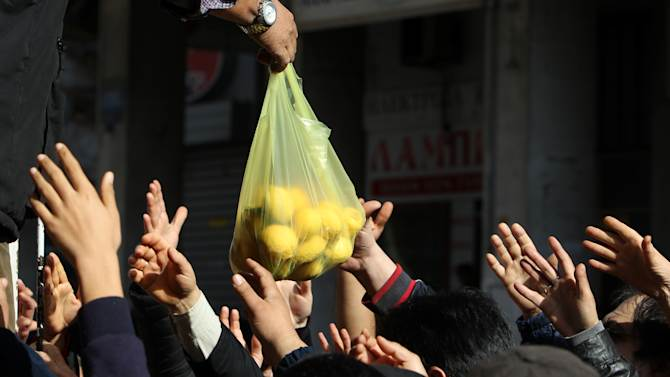 People reach out for fresh produce handouts from fruit and vegetable street market stall holders during a peaceful protest outside the Ministry of Agriculture in Athens, on Wednesday, Feb. 6, 2013. Farmers complain that their production costs are too high, and want Greece's conservative-led coalition government to reduce the price of fuel, scrap plans to increase taxation on agriculture and cut sales tax on their goods. (AP Photo/Thanassis Stavrakis)