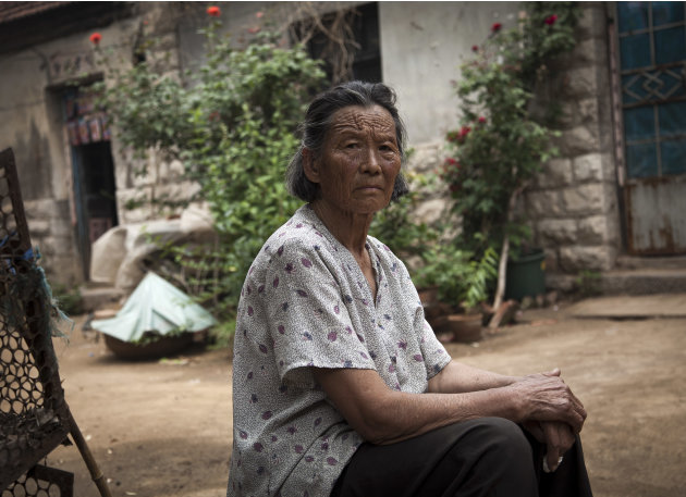 Wang Jinxiang, mother of Chen Guangcheng, takes a rest in the courtyard of her house where Chen was under house arrest, at the Dongshigu village, Shandong province, China, Friday, June 8, 2012. Camera