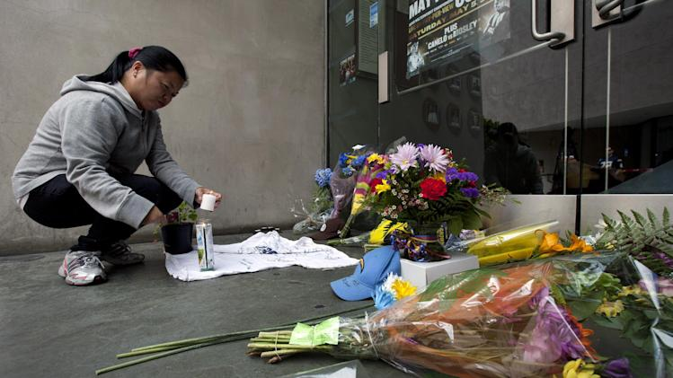 Gemma Estenol lights a candle to leave in front of the doors of former NFL football player Junior Seau's restaurant, Wednesday, May 2, 2012, in San Diego. The former NFL star was found shot to death at his home in what police said appeared to be a suicide. He was 43. (AP Photo/Gregory Bull)