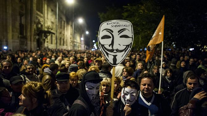 """Thousands of demonstrators protest against an internet tax planned to be introduced by the Hungarian government for the second time in two days in front of the Ministry of National Economy in Budapest, Hungary, Tuesday, Oct. 28, 2014. Tens of thousands of protesters marched Tuesday against a plan by the Hungarian government to tax Internet use from 2015. The inscription on Guy Fawkes mask reads: """"Unity, freedom!"""" (AP Photo/MTI, Janos Marjai)"""