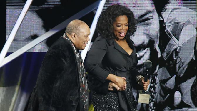Oprah Winfrey, right, leads Quincy Jones, left, on the stage after speaking to induct him into the Rock and Roll Hall of Fame during the Rock and Roll Hall of Fame Induction Ceremony at the Nokia Theatre on Thursday, April 18, 2013 in Los Angeles. (Photo by Danny Moloshok/Invision/AP)