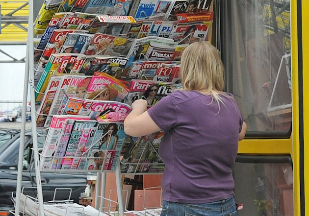 A woman checks magazines at a newspaper stand in Warsaw, Poland, Wednesday, July 18, 2012. Several major Polish media companies are joining forces to put some of their best online content behind a combined paywall, an attempt to maintain revenue as print readership declines. The initiative, known as Piano, has already been implemented with success in Slovakia and Slovenia, where people pay a small one-time fee for unlimited access to a range of websites. Poland, with 19.5 million Internet users in a nation of 38 million, represents the first large market to try this pay model, and how it fares could determine whether it takes hold in other countries. (AP Photo/Alik Keplicz)
