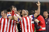 Atletico Madrid's Radamel Falcao (C) celebrates with teammates after scoring during their Spanish La Liga match against Real Sociedad, on October 21, at the Anoeta stadium in San Sebastian. Atletico play Osasuna next, at home, on Sunday